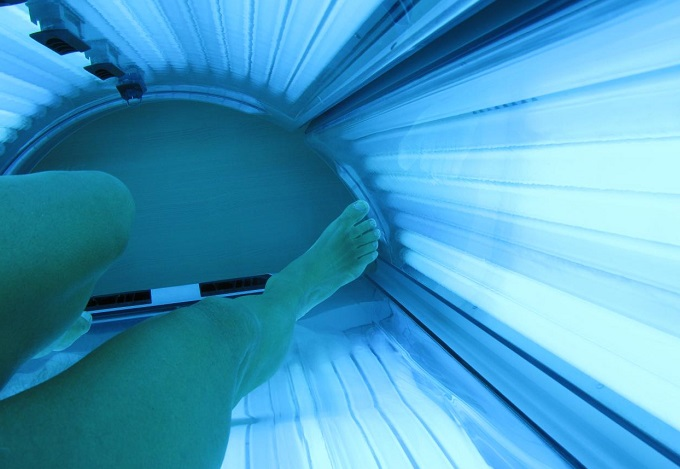 a female laying on a sunbed
